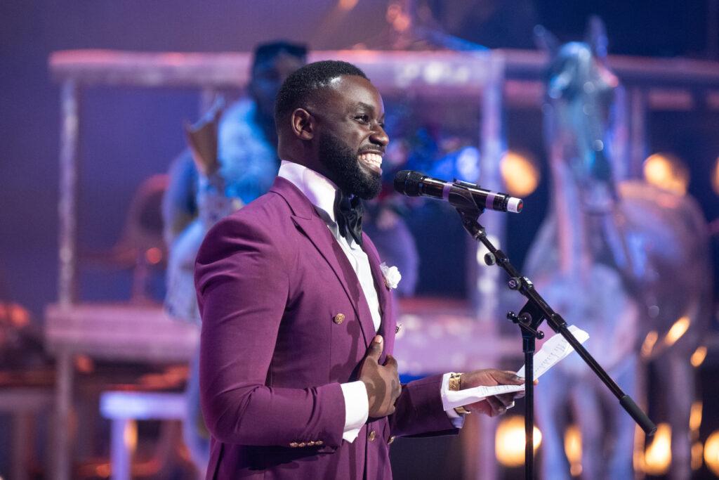 Emmanuel Ohene Boafo staat met een grote glimlach voor een microfoon, in een prachtig violet pak.